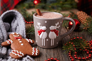Cup of hot chocolate or cocoa with two cute deer, cinnamon and gingerbread man cookie in new year tree decorations frame on vintage wooden table background. Homemade traditional celebration recipe