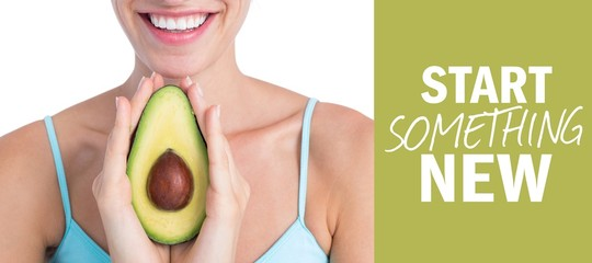 Composite image of attractive woman showing half of an avocado