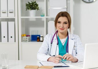 Beautiful friendly female doctor sitting at working table