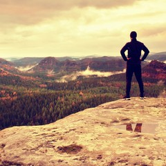 Slim tall tourist on sharp peak of rock in rock empires park is watching over misty and foggy morning valley to Sun
