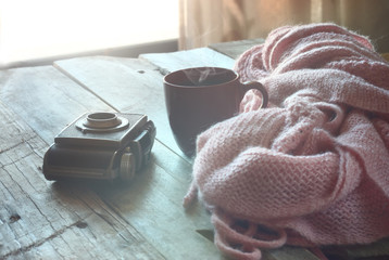 selective focus photo of pink cozy knitted scarf with to cup of coffee next to old photo camera on a wooden table. faded style retro filtered