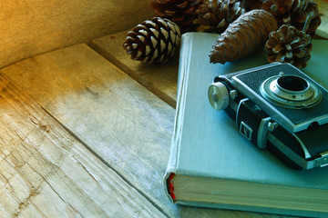 old book, vintage photo camera next to pine cones on wooden table. selective focus