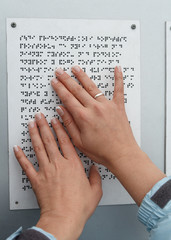 Her hands reading Braille table. Health and social adaptation