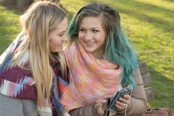 Freundinnen unterhalten sich mit Smartphone
