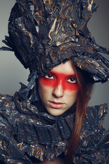 Portrait of beautiful woman with red make-up with metal headwear
