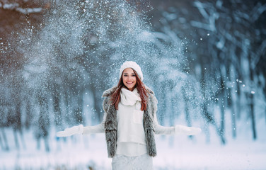 Cute young girl playing with snow