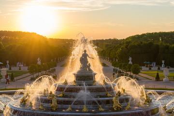 Spoed Fotobehang Fontaine Fontaine de Versailles sur un coucher de soleil