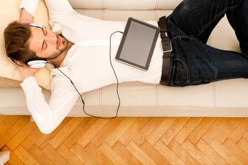 Young man with a Tablet PC on the sofa