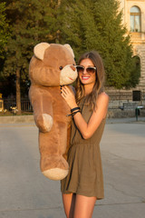 Lovely smiling young woman in knitted clothes holding big soft teddy bear
