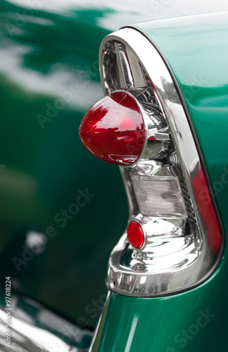 Close-up of cone shape tail lights of a green shiny classic vintage