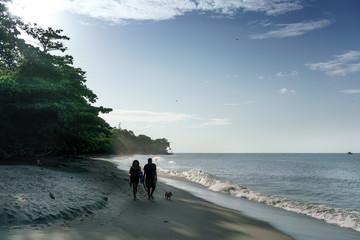 Couple with dog walking on sandy beach, Trinidad, Trinidad and Tobago