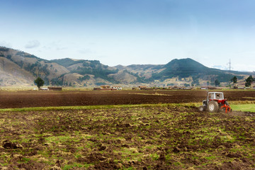 Tractor ploughing field with mountain range in background, Cusco, Peru