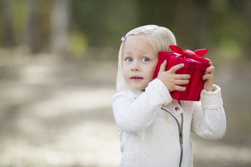 Happy Baby Girl Holding Red Christmas Gift Outdoors.