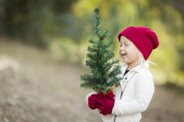 Baby Girl In Red Mittens and Cap Holding Small Christmas Tree