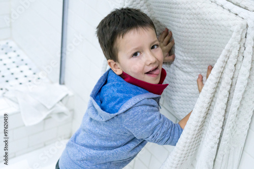 """Cute little child looking at camera and drying his hand ..."