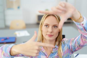 frau schaut konzentriert duch fingerrahmen