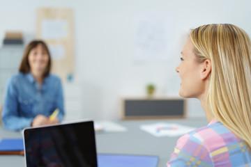 frau unterhält sich mit einer kollegin im büro
