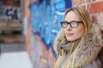 attraktive blonde frau lehnt an einer mauer mit graffiti