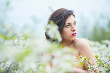 Closeup portrait of a young beautiful sexy brunette woman with white cherry flowers in bokeh background