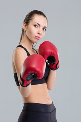 Concentrated young sportswoman in boxing gloves ready to fight
