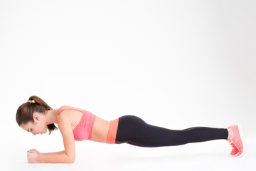 Beautiful focused fitness woman standing in a plank position