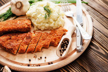 meat with garnish , chicken cutlets in breadcrumbs , boiled mashed potatoes with herbs , garlic and spices on a wooden background