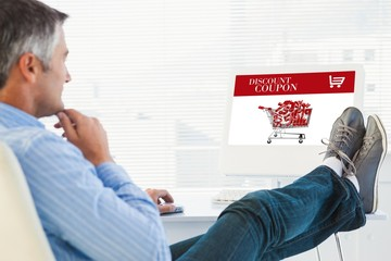 Composite image of relaxed man with feet on desk using computer