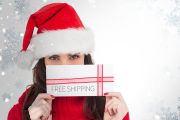 Composite image of festive brunette holding a gift