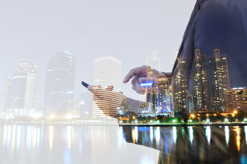 Double exposure of city and business man using digital smartphon
