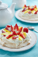 pavlova decorated with mango and strawberry slices
