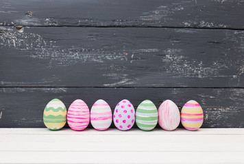 Easter eggs painted in pastel colors on a white wood background