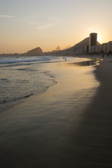 Golden sun setting behind a silhouette of the Rio de Janeiro skyline at the Leme end of Copacabana Beach