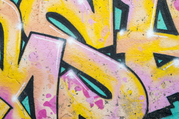 Abstract urban background of graphic letters of a colorful graffiti tag in pink, yellow and blue in the Lapa neighborhood of Rio de Janeiro, Brazil