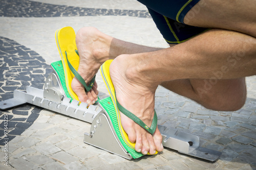 34245ee35c71ca Brazilian athlete wearing flip flops crouching at the start position in running  blocks on the tiles of the Copacabana boardwalk in Rio de Janeiro