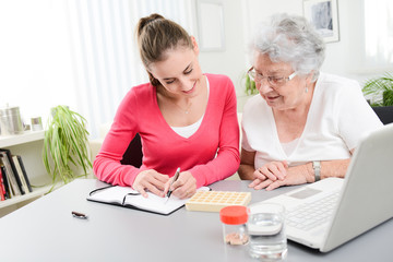 cheerful young woman helping an elderly woman with pills medical prescription