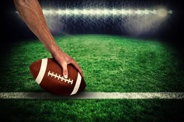 American football player placing ball