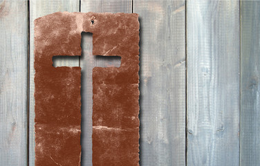 Old vintage Christian paper cross on wood background