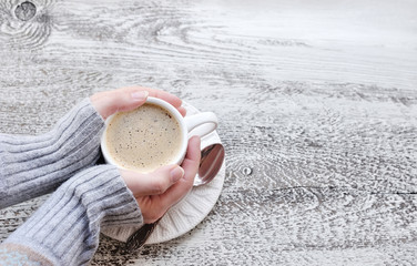 Female hands holding cups of coffee on wooden table background