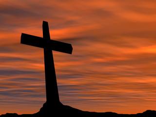 Black cross on mountain at sunset