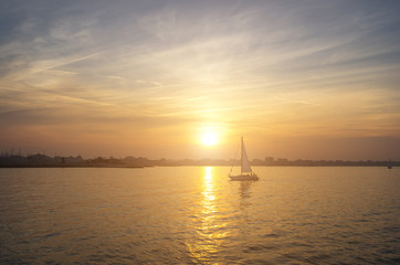 a boat sailing on the sea with the sunset as background - nature, transportation and lifestyle concept