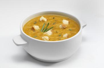 Овощной суп-пюре с гренками в фарфоровой тарелке на белом фоне