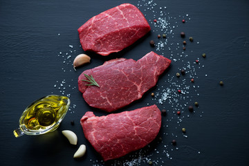Deurstickers Vlees Fresh uncooked marbled meat steaks over black wooden surface