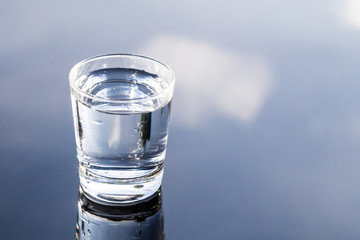 Refreshing purified water in transparent glass with reflection against blue sky and cloud