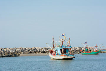 Two fishery boats floating on clam blue sea wity clear blue sky.