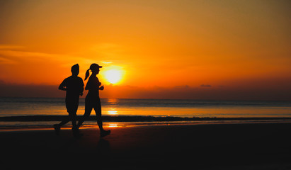 Young couple: man and woman run together on a sunset on lake coa
