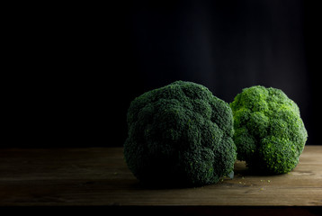 Broccoli on a Wooden Table with Black Background. Dark Rustic Old Style