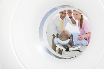 Doctor and technician nurse preparing patient at CT scanner tube in hospital