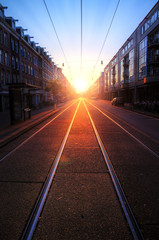 Early morning sunrise on the streets of Amsterdam with a nice perspective and depth with the tram rails
