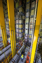Worker below foodstuffs merchandise stored in automated storage and retrieval systems warehouse stack