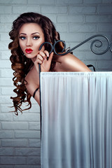 Beauty Sexy Young Woman peeps from Dressing room, Beautiful Glamour Fashion Brunette Lady with long curly hair, red plump lips, blue eyes